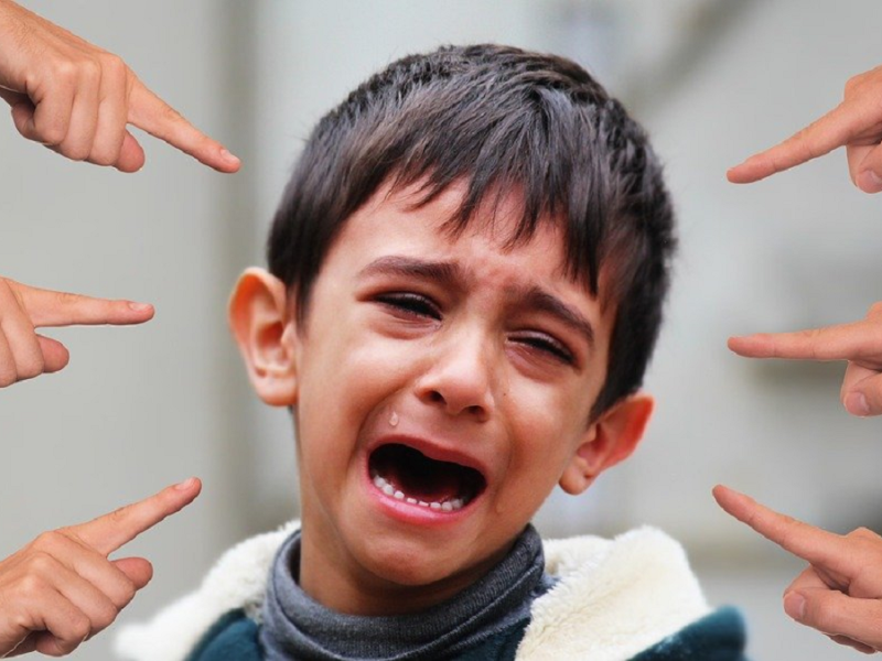 Crying child with hand all around him pointing fingers - meant to represent Xenophobia